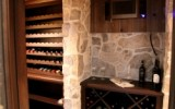 Rubble buff wine cellar with wood accents